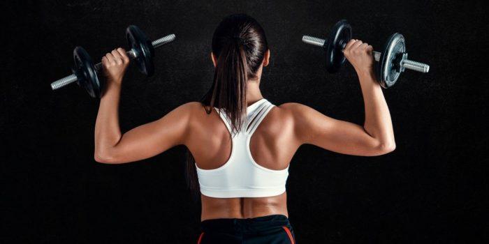 femme de dos soulevant des poids sur les épaules