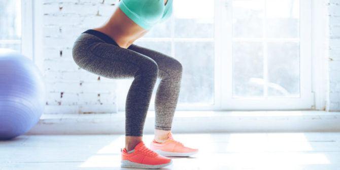 jambes de femme sportive en position squat