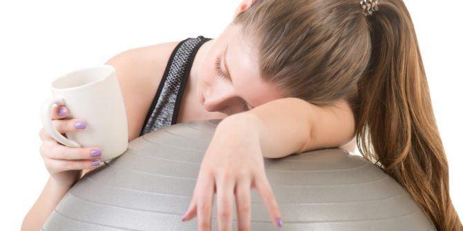 femme endormie sur un ballon qui manque d'énergie, un café à la main