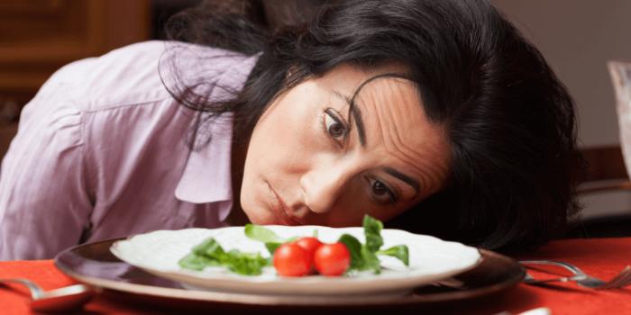 femme désespérée devant une assiette presque vide