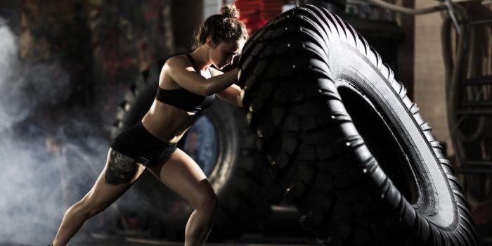 femme qui pousse un gros pneu