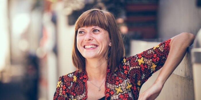 femme qui sourit assise sur un banc